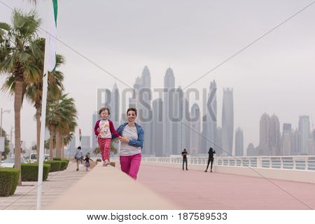 young mother and cute little girl running and cheerfully spend their time on the promenade by the sea with a big city in the background