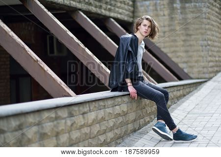Portrait of young handsome man, city outdoor. Attractive trendy fashion 18 years old teen boy posing outside