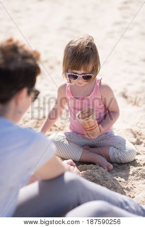 cool young mom and her little girl playing with a bucket full of sand wearing sunglasses and relaxing on the beach on a sunny day