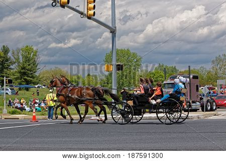 LANCASTER PA - MAY 14 2017: An Amish carriage passes the Make-A-Wish Foundation truck convoy. On the Mother's Day annual fundraiser truckers grant a Lancaster County wish ride to children with life-threatening illnesses.