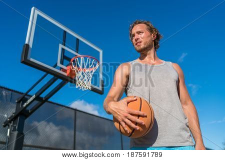 Basketball playing man on court with ball. Athlete player portrait with net in background.