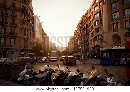 BARCELONA - JULY 29, 2016: Traffic and parked scooters on Plaça de Catalunya