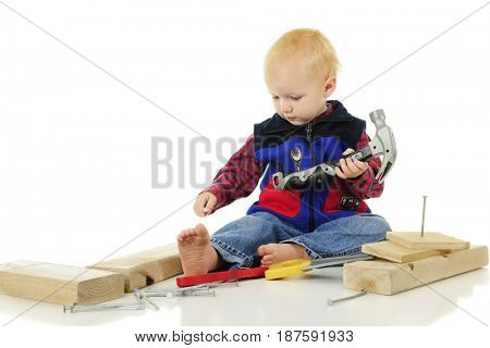 An adorable toddler about to place a large nail between his toes.  He holds a toy hammer and is surrounded by wood blocks and large nails.  On a white background.