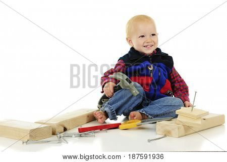 A delighted toddler boy surrounded by toy tools, long nails and blocks of wood.  On a white background with plenty of space for your text on upper left.