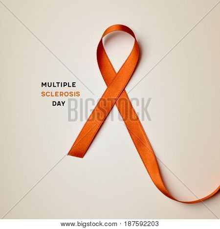 the text multiple sclerosis day and an orange ribbon on a beige background