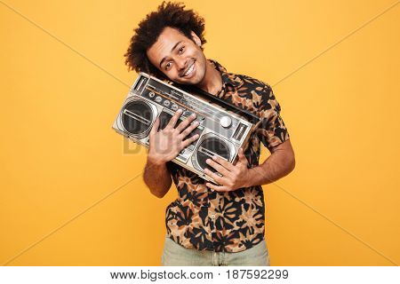 Image of young smiling african man standing with tape recorder isolated over yellow background. Looking at camera.