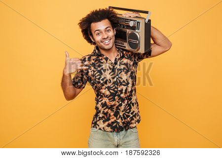 Portrait of a smiling african man in summer clothes holding boombox on his shoulder isolated over yellow background