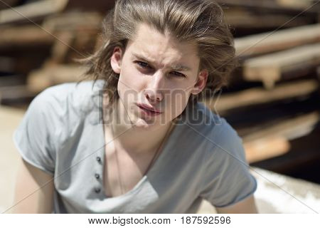 Portrait of young handsome man over wood boards, outdoor. Attractive trendy fashion 18 years old teen boy posing outside over construction waste, image toned.