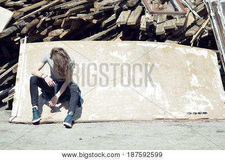 Portrait of young handsome man over wood boards, outdoor. Attractive trendy fashion 18 years old teen boy posing outside over debris