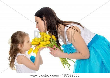Beautiful young mother and little daughter in the same blue long skirts tutus , standing sideways to the camera , admiring the bouquet of yellow tulips.Little girl enjoying the smell of flowers.Isolated on white background.