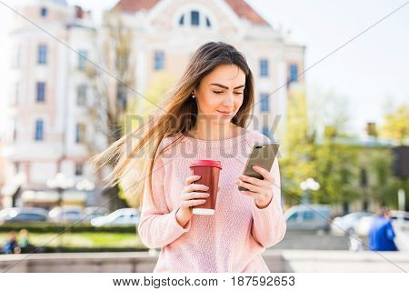 Young Woman Standing At The Sunny Street Drinking Coffee To Go And Using Mobile Phone