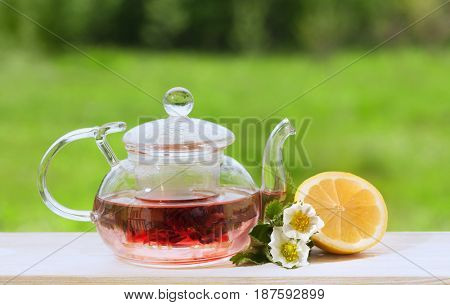 Teapot with fragrant herbal tea on a background of nature lemon and strawberry flower