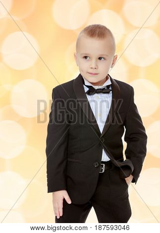 Beautiful little blond boy in a fashionable black suit with a tie.Brown festive, Christmas background with white snowflakes, circles.