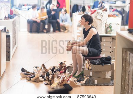 Woman Chooses  Shoes At Fashionable Shop