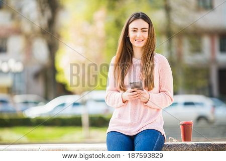Young Woman With Phone Browse In Internet And Drink Coffee In The City Street