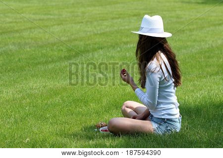 Young female in white fashion attire sitting in grassy park eating fruit