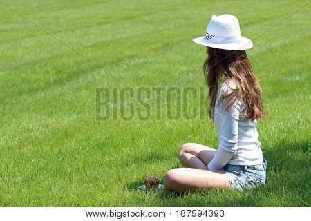 Female seated in grassy park in summer white attire eating picnic food