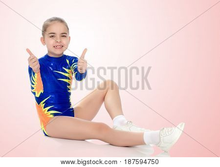 A charming gymnast girl, a younger school age, in a beautiful blue swimsuit, performs an exercise on the floor.She looks directly into the camera and shows her thumb. The gesture is okay.Pale pink gradient background.
