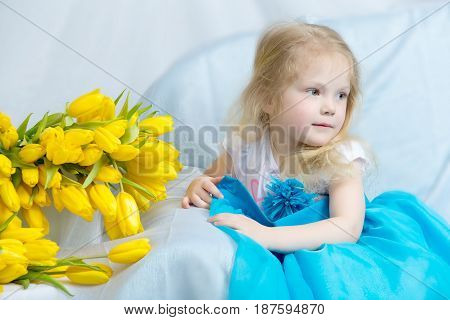 Cute little blonde girl in blue long dress sitting on a sofa beside a large bouquet of yellow tulips.
