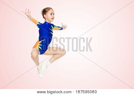 Beautiful Russian girl gymnast younger school age, in blue in a sports swimsuit.She performs a complex leap.Pale pink gradient background.