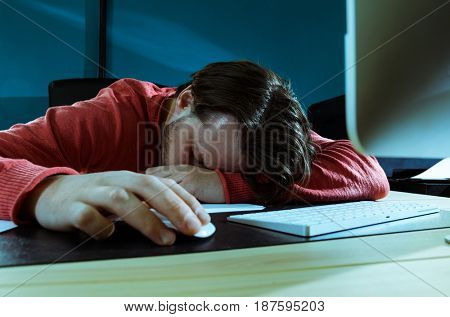 Tired businessman sleeping at his office desk with computer