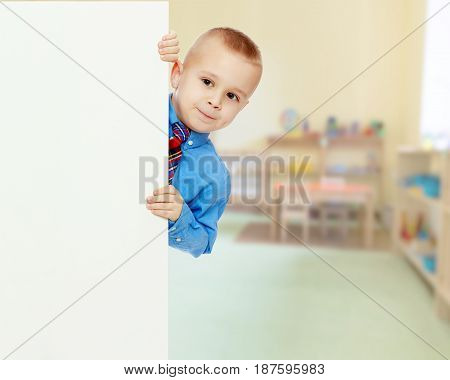 Beautiful little boy in a blue shirt and tie peeking from behind the banner.In the Montessori room the children's garden where there are shelves with toys and material.