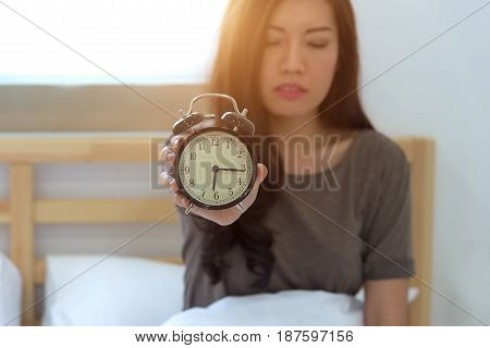 Young sleeping woman and alarm clock in bedroom at home. focus alarm clock