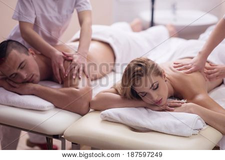 Relaxed young beautiful couple receiving a back massage from masseur in a spa