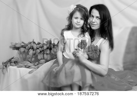 Beautiful young mother and little daughter in the same blue dresses on the sofa with a bouquet of flowers.Black-and-white photo. Retro style.