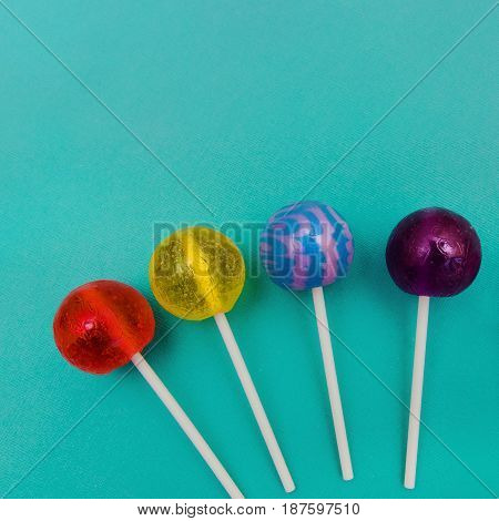 Lollipop Flat lay Minimal concept Four colorful round lollipops are lying on a light blue background One-color and two-color candies