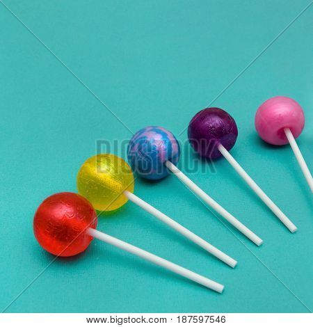 Lollipop Flat lay Minimal concept Five colorful round lollipops are lying on a light blue background One-color and two-color candies