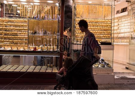 young mother with a cute little girl in a stroller in front of the window jewelry shop