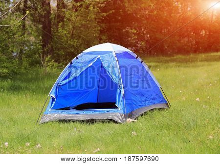 Blue tourist tent on green meadow