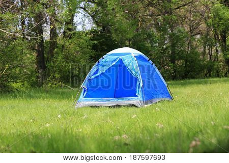 nice tourist tent on green meadow in forest