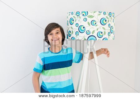 Boy standing next to lamp