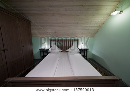 Interior of room with double bed and wardrobe in hotel.