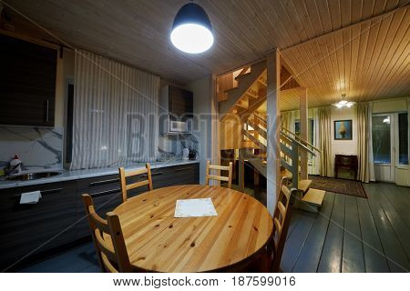 Kitchen zone with table, chairs and working area in wooden house.