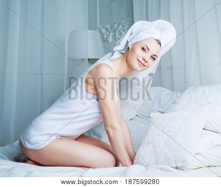 beautiful young woman with a towel on her head after washing her hair