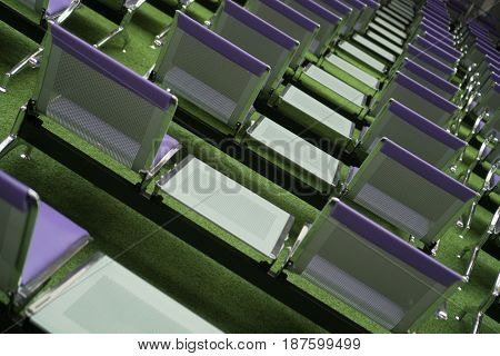 Back view of steel chairs covered with purple leather with small table between, set for an outdoor event