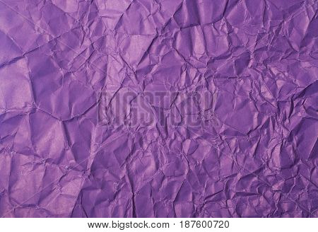 Close-up fragment of a violet crumpled paper texture as a backdrop composition