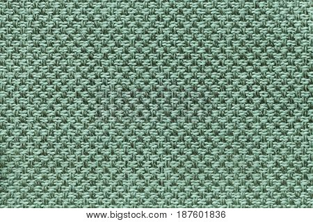 Light turquoise background with checkered pattern closeup. Structure of the green fabric macro.