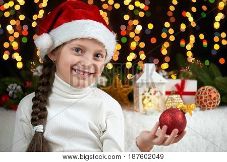 child girl portrait with christmas decoration, dark background with lights, face expression and happy emotions, dressed in santa hat, winter holiday concept