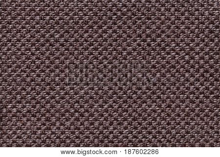Dark brown background with checkered pattern closeup. Structure of the umber fabric macro.