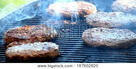 Beef hamburgers on the grill outdoors cooking.