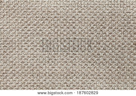 Light brown background with checkered pattern closeup. Structure of the beige fabric macro.