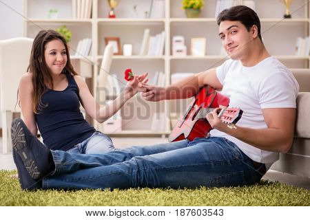 Romantic pair playing guitar on floor