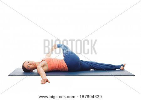 Woman doing Hatha Yoga asana Parivrtta ardha pawanmuktasana - Revolved knee-to-chest Pose back stretch isolated on white background