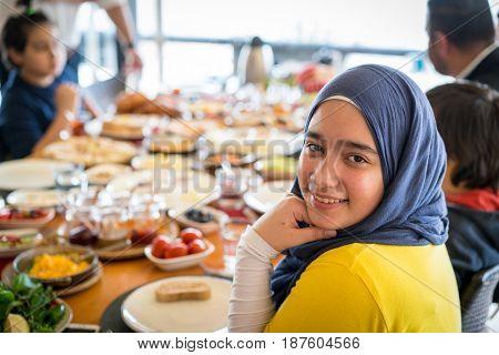 Happy muslim girl eating breakfast