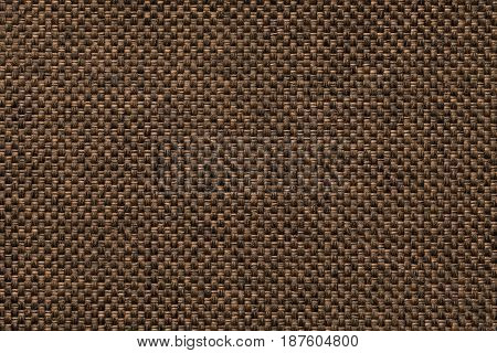 Dark brown woolen background of dense woven bagging fabric closeup. Structure of the ginger cloth with natural texture. Cloth backdrop.