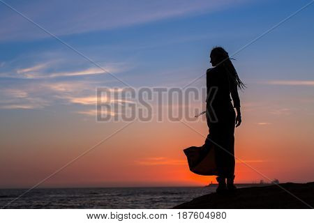 Silhouette of young woman in dress standing by the sea at amazing sunset.